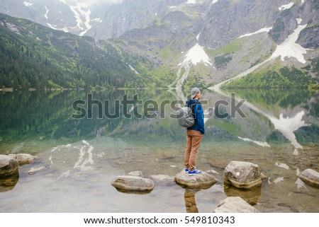 man relaxing on the lake and mountains sunny landscape.