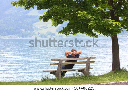 man rest on the bench on a coast lake
