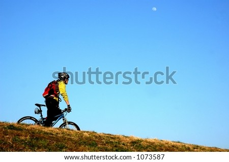 Man riding his bike alone and white moon on the sky