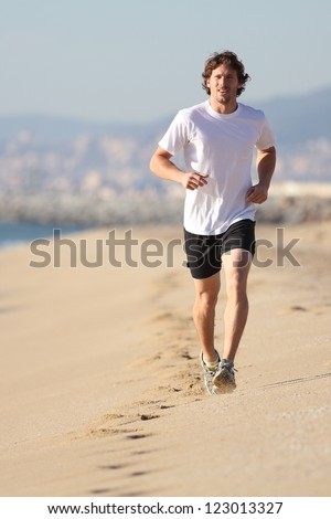 Man running in the beach. Front view