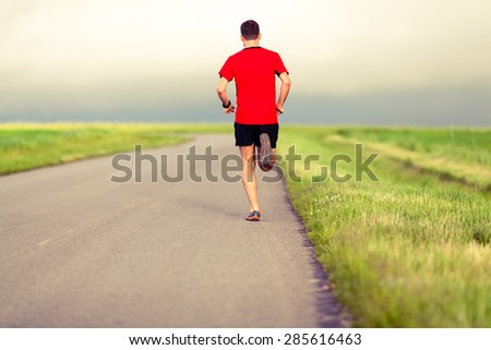 Man running on country road, healthy fitness lifestyle, sport speed training beautiful landscape. Young runner jogging training and doing workout exercising power walking outdoors in nature.