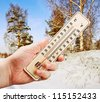 man's hand holding a thermometer with low against the cold of the winter forest - stock photo