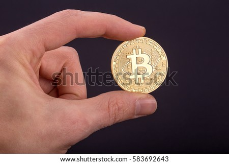 Mans Hand Holding Golden Bitcoin On Black Background