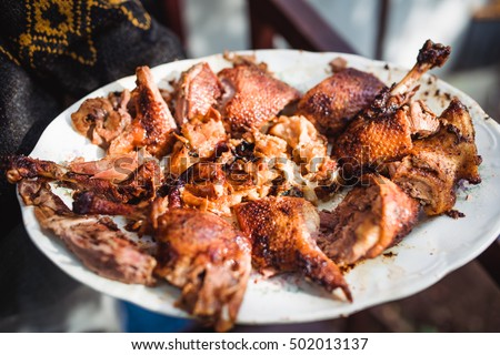 man's hand holds grilled roast chicken on white plate