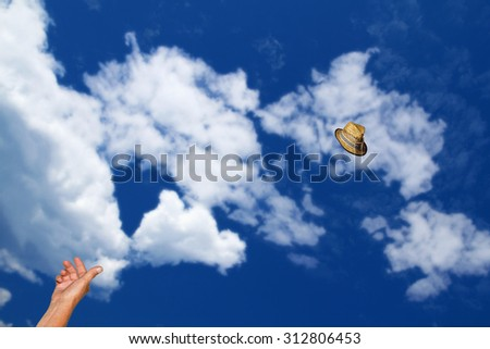 Man's hand is throwing straw hat far away to the sky