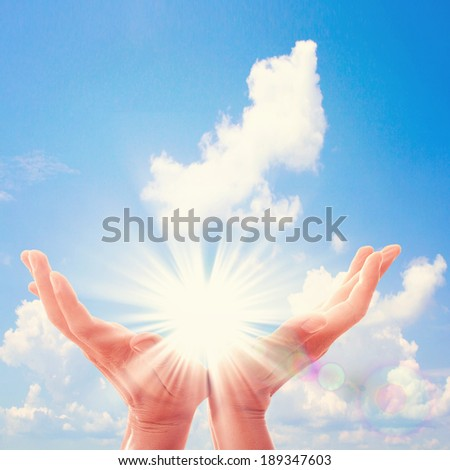 Man's hands reach for sky. Prayer at dawn. Sunny landscape, beautiful sky.