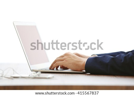 Man's hands using laptop at the table in office
