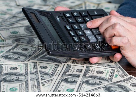 Man's hands with money and calculator. Money saving concept.