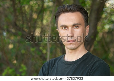 Man's portrait in the soft forest background