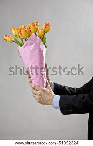 Man's two hands holding a bouquet of orange tulips