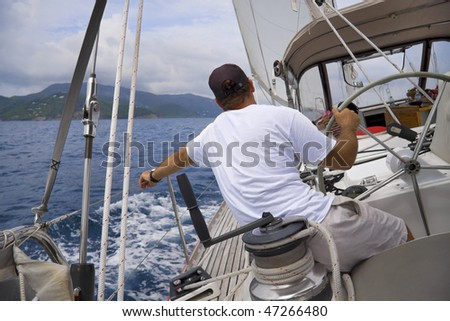 Man sailing a sailboat in the tropics with tropical mountain in background.