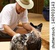 man shampoos dog outdoors - stock photo