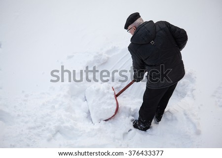Man shovelling fresh snow  with a red shovel