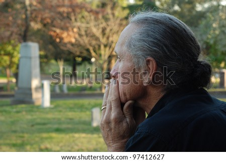 Man sitting at gravesite with a look of sadness.