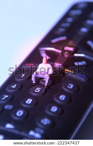 Man sitting on a remote control and watching TV