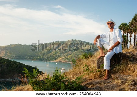 man sitting on a rock and looking at the sunset of Phuket