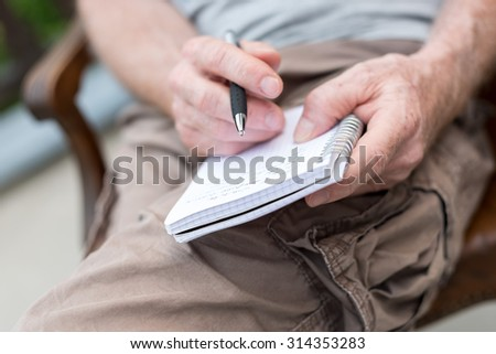 Man sitting outdoor taking notes on a pocket book
