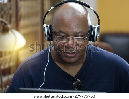 man sitting relaxing and listening to music from his laptop.