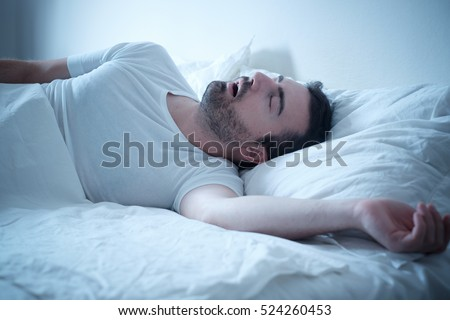 Man sleeping in his bed and snoring loudly
