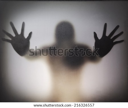 Man standing behind frosted glass