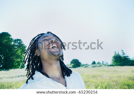 Man standing outdoors looking up smiling