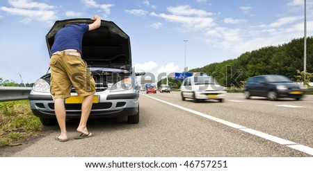 Man staring down at the engine of his stalled car on the hard shoulder of a motorway