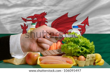man stretching out credit card to buy food in front of complete wavy national flag of wales