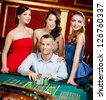Man surrounded by women gambles roulette at the casino - stock photo