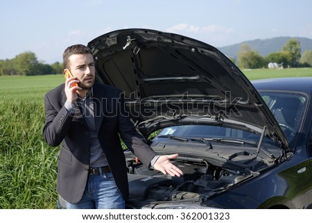 man talking on a cell phone by a broken car