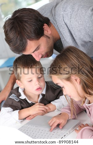 Man teaching kids how to use laptop computer