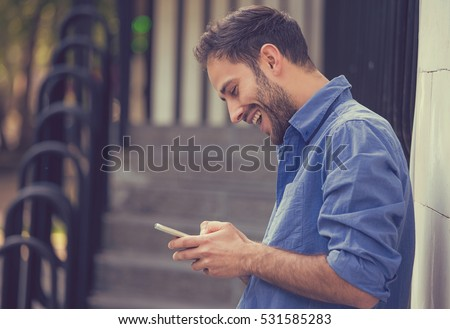 Man texting on phone. Casual urban professional entrepreneur using smartphone smiling happy outside office building. Outdoor portrait of modern young guy with mobile in the street