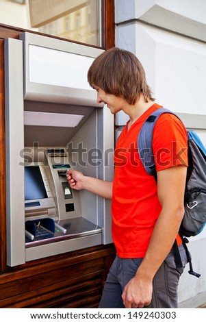 Man tourist puts bank card into the ATM
