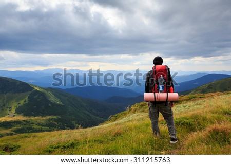 Man traveler hiking in the mountains with a large tourist backpack. Standing back. Admiring the beautiful scenery of Ukrainian Carpathian Mountains. Dramatic cloudy sky.
