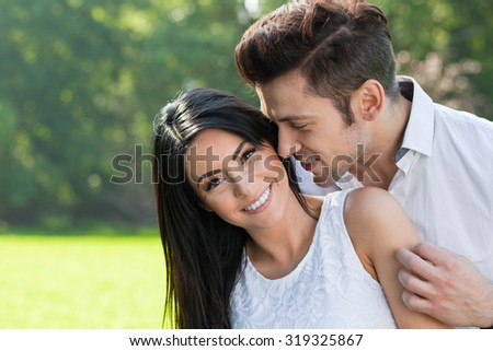 man trying to kiss his laughing girlfriend