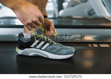 Man tying shoelaces at sneaker
