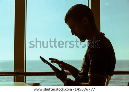 Man Using Digital Tablet on a Ferry Boat