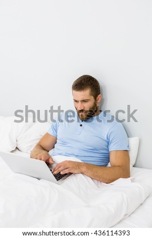 Man using laptop on bed in bedroom