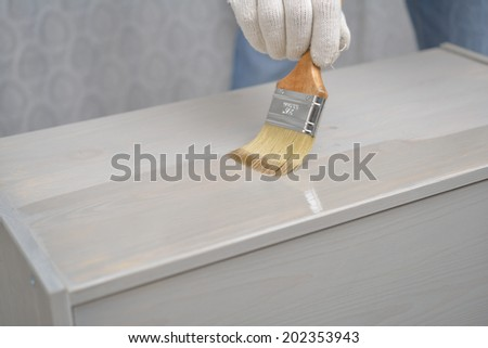 Man varnishing the wooden chest