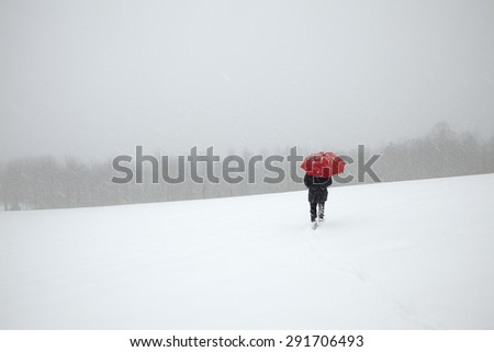 Man walking in winter snow storm in the snow