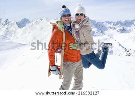 Man walking through snow carrying a sled on his back and lifting girlfriend