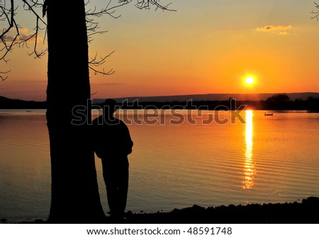 man watching fisherman at sunset