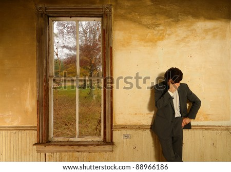 Man wearing a suit props his head against his hand in despair at a vintage home