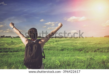 Man winner traveler on the meadow with green grass and blue sky