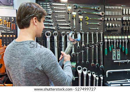 Man with a big wrench on the background wall with tool in store