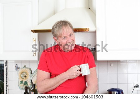 man with a cup of coffee in the kitchen