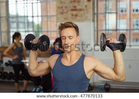 Man with closed eyes pushing up dumb bell weights at indoor gym with brick walls and large windows