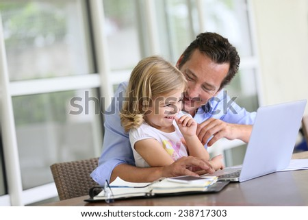 Man with daughter looking at internet on laptop