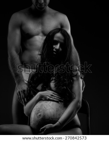 Man with naked torso with pregnant woman posing in studio