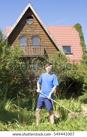 Man with rake cleaning garden near country house.