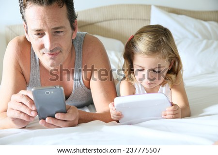 Man with smartphone and daughter playing with child's tablet